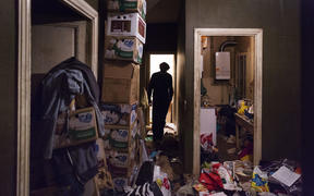 A man with diogenes syndrome or compulsive hoarding lives alone in his garbage-filled apartment in the city.