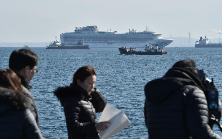 The Diamond Princess cruise ship (top,C) is seen off the port of Yokohama on February 5, 2020. - At least 10 people on a cruise ship quarantined off the coast of Japan have tested positive for the new coronavirus, Japan's health minister said on February 5.