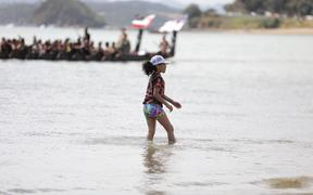 A girl walking in the water.