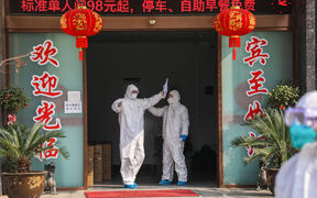 Medical staff member (left) being disinfected by a colleague before leaving a quarantine zone converted from a hotel in Wuhan, 3 February 2020.