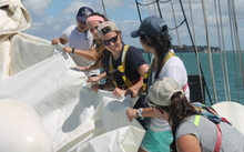 An image of several SEA students working together to fold a sail.