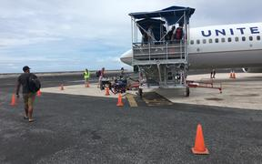 The Marshall Islands on Friday indefinitely banned all overseas travel by government employees and elected leaders in an effort to reduce opportunities for the importation of the new coronavirus. Pictured: Passengers boarding a United Airlines flight in Majuro.