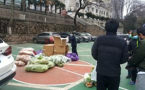 Members of the International Students Office at Wuhan University of Technology provide vegetables to students who have remained on campus.