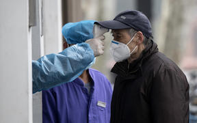 An elderly man wearing a face mask has his temperature checked before entering a community hospital in Shanghai on 13 February 2020.