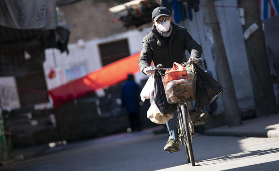 A man rides a bike in a street in Wuhan, Hubei province, 16 February 2020.