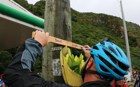 A cyclist writes on the tribute cross on the side of the Hutt Road.