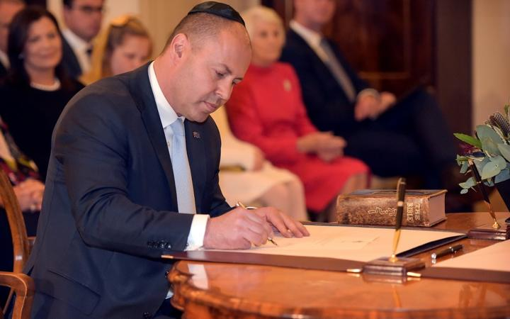 Australian Treasurer Josh Frydenberg signs a document during an oath-taking ceremony at Government House in Canberra on May 29, 2019.