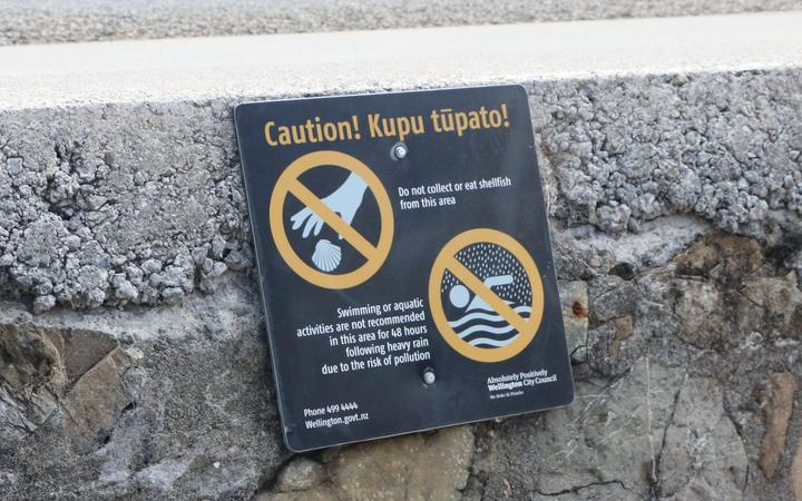 A sign at Ōwhiro Bay warns people not to take shellfish or swim after rain. Karori residents want similar signs to warn people to stay out of the polluted stream, but Wellington Water has refused to erect any.