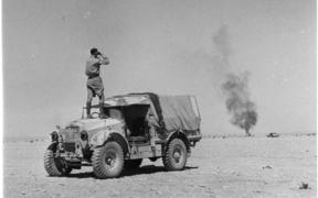 Mobile Unit commentator Arch Curry standing on a jeep at Alamein, viewing a burning New Zealand jeep through binoculars