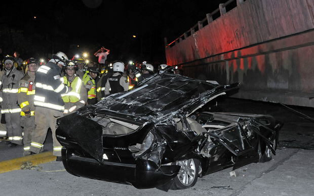 Rescue workers stand before a destroyed car crushed by a bridge which collapsed in the 7.8 magnitude quake.