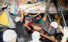 Rescue workers work to pull out people trapped in a building in Manta.