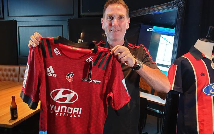Crusaders fan Anthony Mercer hold a jersey with the team's new logo.