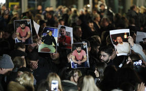 Mourners hold up photos, believed to be of vicitims, during a vigil close to a crime scene in Hanau, near Frankfurt.