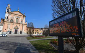 "A municipal information sign reads ""Coronavirus, the population is invited as a precautionary measure to remain at home"" is pictured in the village of Casalpusterlengo, southeast of Milan"