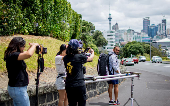 The film crew filming Kareem Adel Ismail leaving the Gladstone Tennis Club with Auckland cityscape in the background..