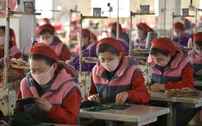 Workers of Songyo Knitwear Factory in Pyongyang produce masks for protection against the coronavirus.