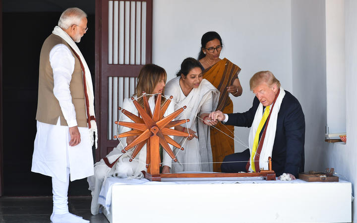 US President Donald Trump holds a string while checking a charkha, or spinning wheel, as First Lady Melania Trump and India's Prime Minister Narendra Modi look on during their visit at the Gandhi Ashram on 24 February, 2020.