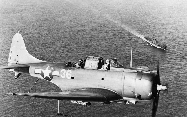 An SBD Dauntless flying over the USS Enterprise.