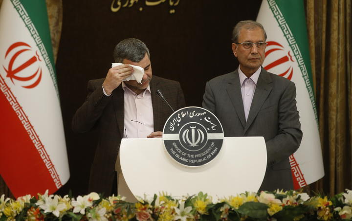 Iranian Deputy Health Minister Iraj Harirchi, left, wipes his brow during a media conference.