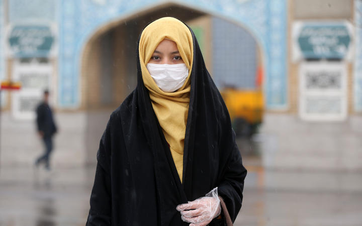 A woman wears a respiratory mask after deaths and new confirmed cases revealed from the coronavirus in Qom, Iran on February 25, 2020.