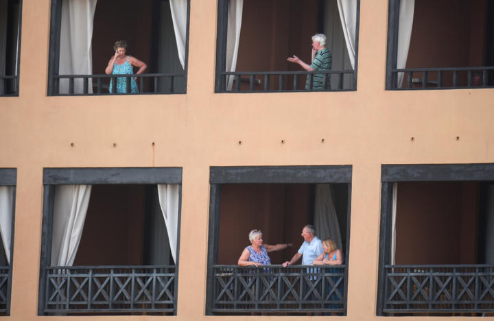 Tourists stand on the balconies of their rooms at a hotel in Tenerife, in Spain's Canary Islands. Hundreds of people were confined to their rooms after an Italian tourist was hospitalised with a suspected case of coronavirus.
