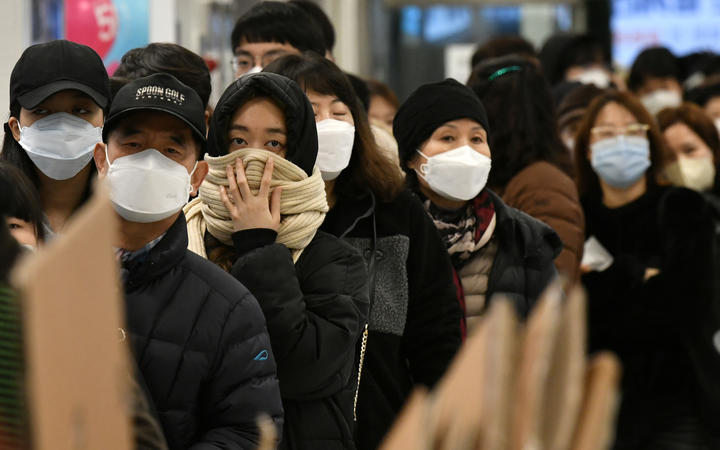 People wait in a line to buy face masks at a shop in the city of Daegu, South Korea, 22 February 2020.