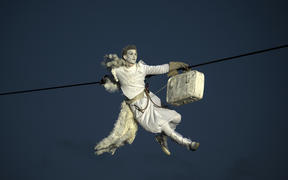 "A performer is suspended from high-wires during the outdoor aerial performance of the show ""Place des Anges"" (Angels' square)."