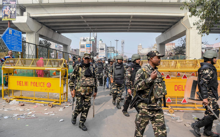 Security personnel patrol on a street following clashes between people supporting and opposing a contentious amendment to India's citizenship law, in New Delhi on February 26, 2020.