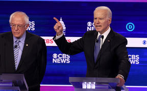 Democratic presidential candidate former Vice President Joe Biden speaks as Bernie Sanders looks on during the debate at the Charleston Gaillard Center on February 25, 2020.