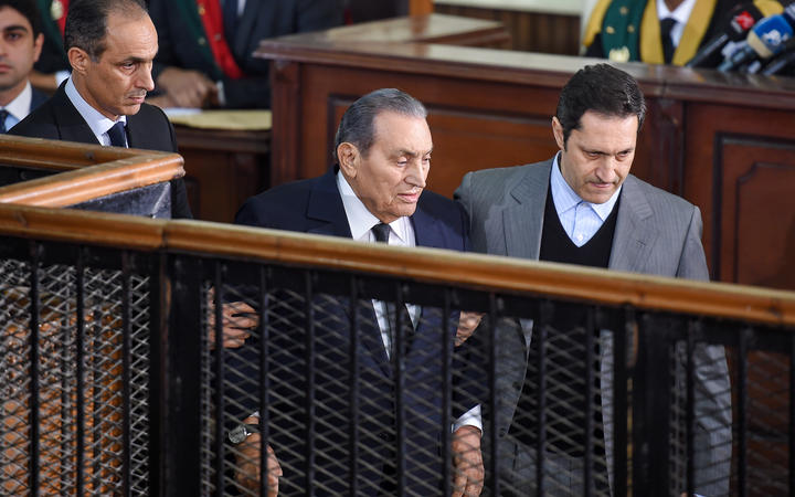 Former Egyptian president Hosni Mubarak, who was ousted following a popular uprising in 2011, being escorted by his two sons Alaa (right) and Gamal (left) as he testifies during a session in the retrial of members of the now-banned Muslim Brotherhood on December 26, 2018.
