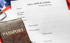 Passports, American flag and visa application form on table. Immigration to USA.