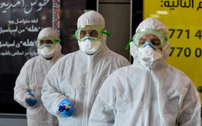 A medical team wearing protective outfit awaits to check Iraqi passengers returning from Iran upon their arrival at the Najaf International Airport on February 21, 2020.