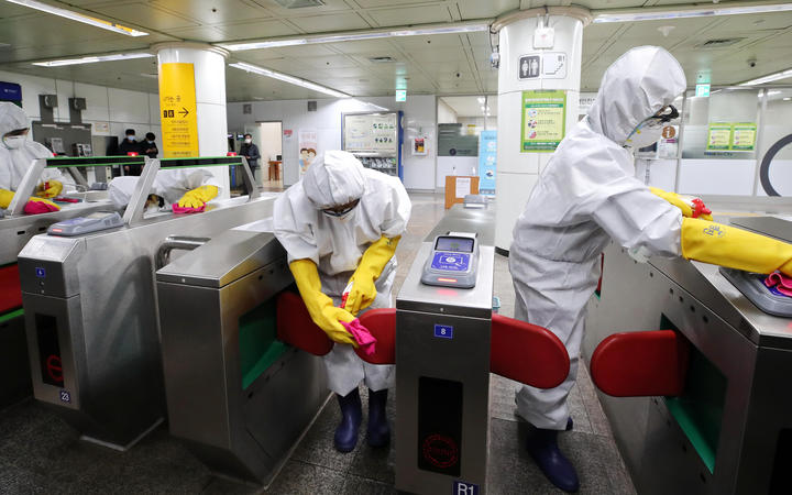 Workers wearing protective gear disinfect ticket gates as part of preventive measures against the spread of the Covid-19 coronavirus, at a subway station in Seoul on February 28, 2020.