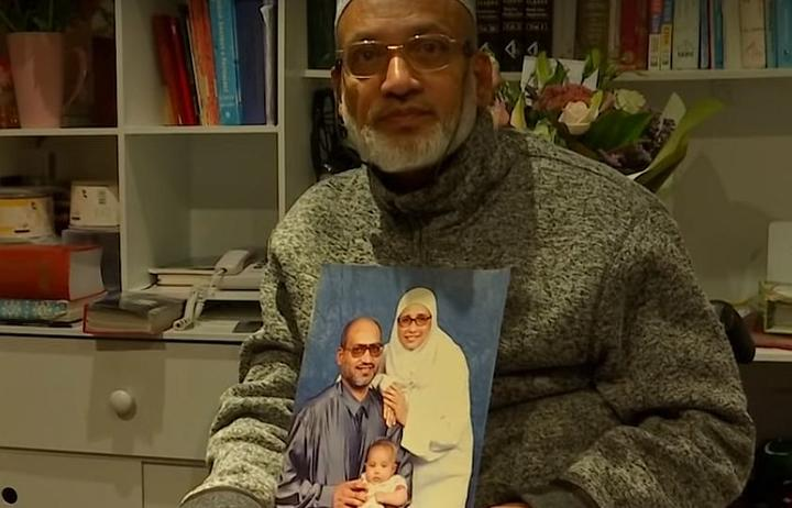 Farid Ahmed holds a picture of his family