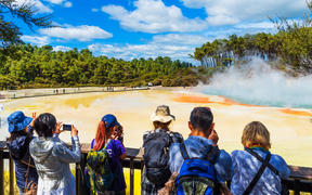 A group of people visiting the geothermal pools in Wai-O-Tapu park.