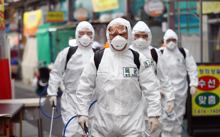 South Korean soldiers wearing protective gear spray disinfectant as part of preventive measures against the spread of the COVID-19 coronavirus, at a market in Daegu.
