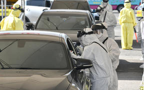 "Medical staff wearing protective gear at a ""drive-through"" virus test facility in Goyang, north of Seoul, 29 February 2020."