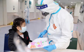 A nurse Yang Liu receiving a painting as a gift from a child infected with novel coronavirus pneumonia at a ward in Wuhan Children's Hospital in Wuhan.