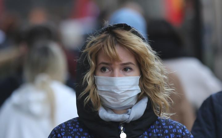 Une femme à Londres porte un masque par précaution contre le coronavirus.