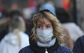 A woman in London wears a mask as a precaution against coronavirus.
