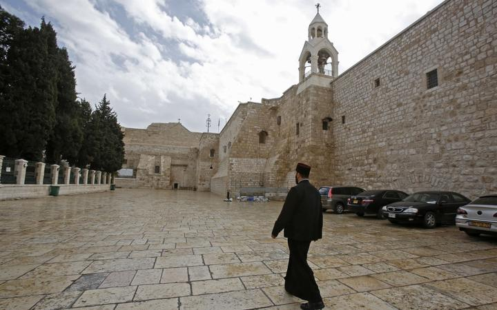 A priest walks past the Church of the Nativity in the West Bank city of Bethlehem, a day after spraying sanitisers as a preventive measure against the coronavirus, on March 6, 2020.