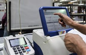 A worker tests the voting machines that will be used in the upcoming presidential elections, during an audit in Caracas on May 14, 2018.