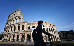 A tourist wearing a respiratory mask as part of precautionary measures against the spread of the new COVID-19 coronavirus, walks past the closed Colisseum monument in Rome.