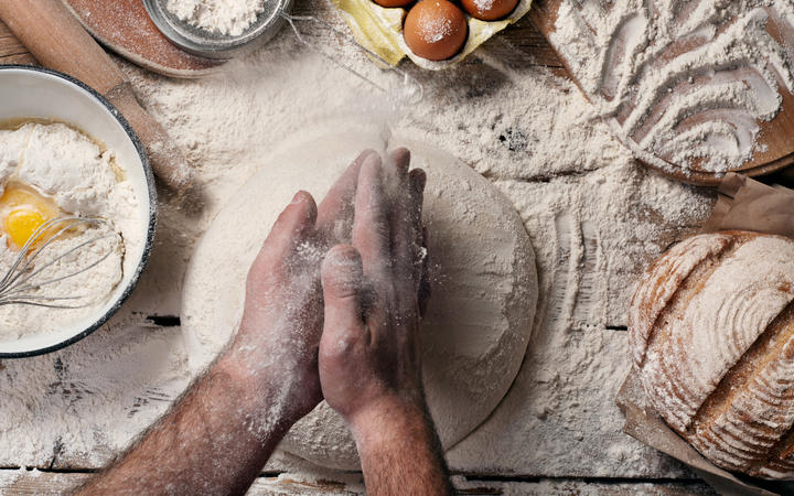 Male baker slaps on dough. Male baker prepares bread. Making bread. Top view. Rustic style