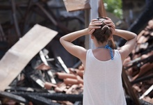 A woman stands with her heads on her hands in front of her burned home.
