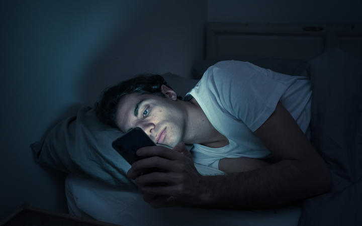 Addicted man chatting and surfing on the Internet with smart phone late at night in bed. Bored, sleepless and tired in dark room with moody light. In insomnia and mobile addiction concept.