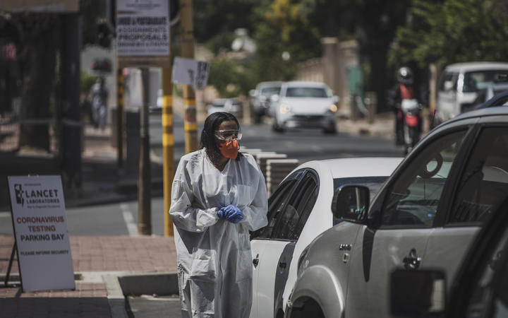 A health professional conducts a COVID-19 coronavirus test at a drive through testing site outside the Lancet Laboratories facilities in Johannesburg.