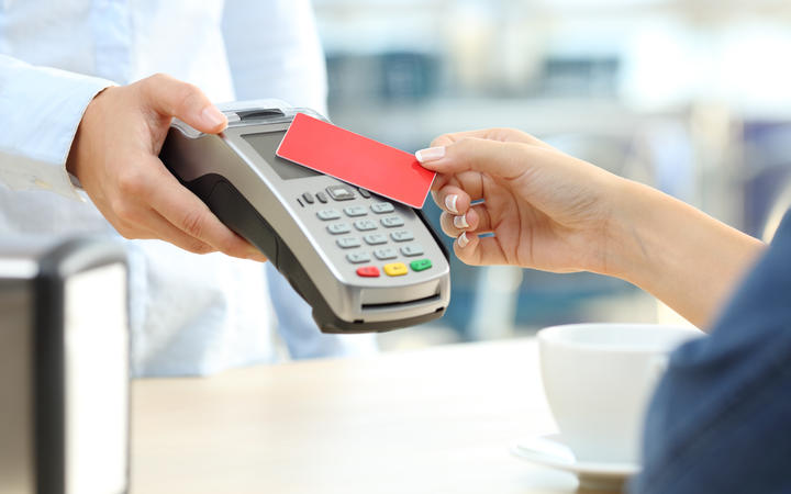Close up of a customer hand paying with a contactless credit card reader in a bar