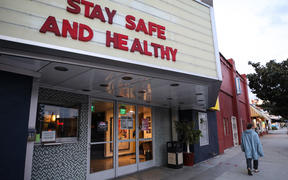 A pedestrian walks past a shuttered movie theater, with the message 'Stay Safe and Healthy' displayed on the marquee.