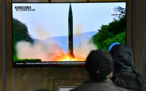 People watch a television news broadcast showing a file image of a North Korean missile test, at a railway station in Seoul on March 21, 2020. - North Korea on March 21 fired two projectiles presumed to be short-range ballistic missiles into the sea off its east coast, Seoul's military said.